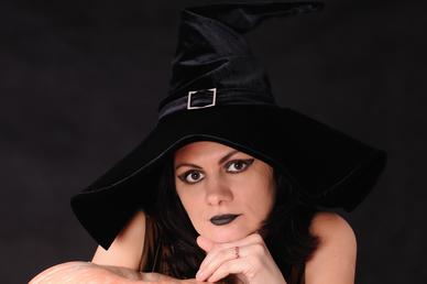 Young witch with a pumpkin on a black  background